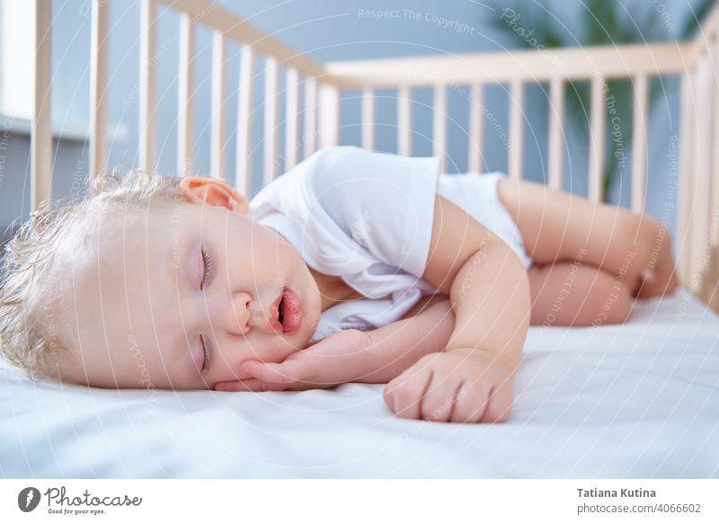 Baby schläft in Baby Holzbett für Neugeborene. Ein geräumiges, helles Zimmer mit einer Dattelpalme im Hintergrund. Raum kopieren Kleinkind Säugling Bett