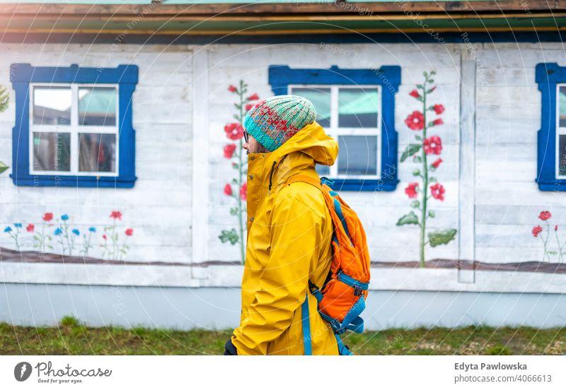 Reisender Mann vor einem traditionellen Holzhaus, Polen kalt Winter Rucksack Backpacker Tourist jung ländlich Volkskunst Sehenswürdigkeit polnisch