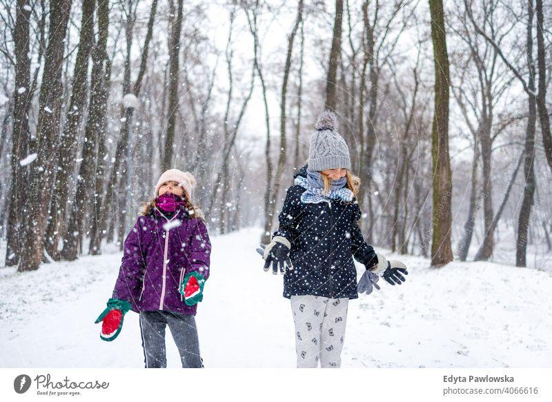 Kinder werfen Schnee in die Luft und genießen einen kalten Wintertag Werfen Tochter zwei Lachen Freunde Genuss Aktivität spielerisch genießend spielen Lächeln