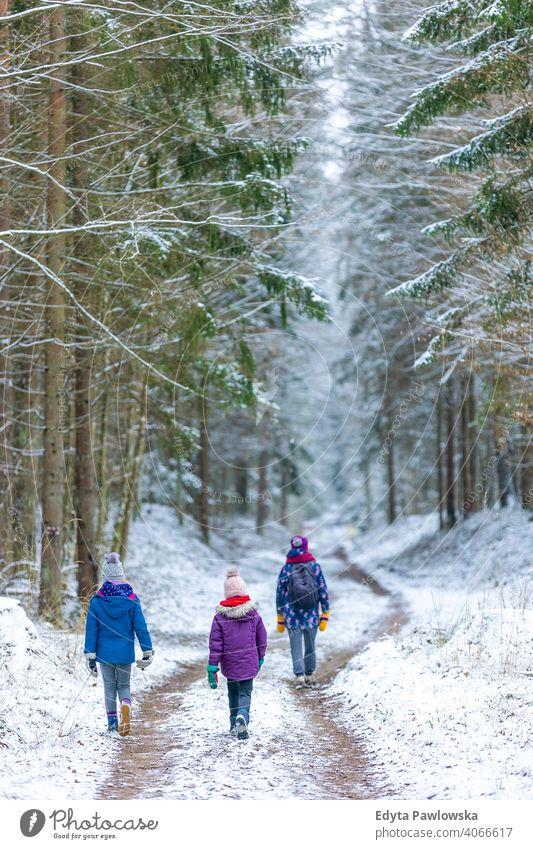 Mutter und Kinder genießen einen gemeinsamen Winterspaziergang durch den Wald im Freien Zusammensein Familie Abenteuer aktiv Tourist Mädchen Frau Aktivität