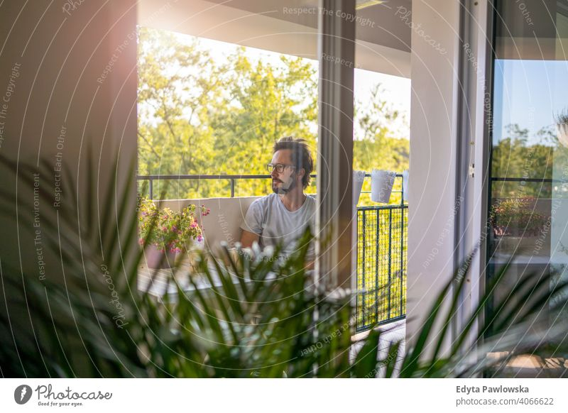 Mann trinkt Kaffee auf dem Balkon seiner Wohnung Frischluft ruhen Quarantäne Topfpflanze zu Hause bleiben Brille Sperrung einfaches Leben Terrasse