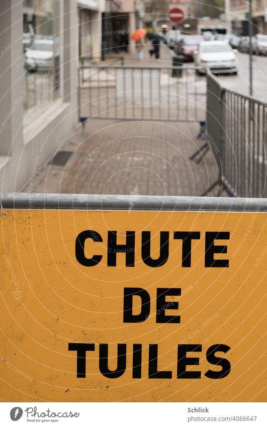 Vor einer Absperrung steht auf einem gelben Schild in französischer Sprache CHUTE DE TUILES Dachdeckerarbeiten oder Sturmschaden Chute de Tuiles Gehweg