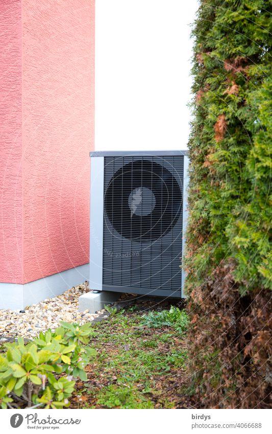 Luftwärmepumpe im Vorgarten eines Wohnhauses. Luftwasserwärmepumpe Hausecke Luft-Wasser-Wärmepumpe Umweltschutz Heizungsergänzung Ventilatoren Pflanzen
