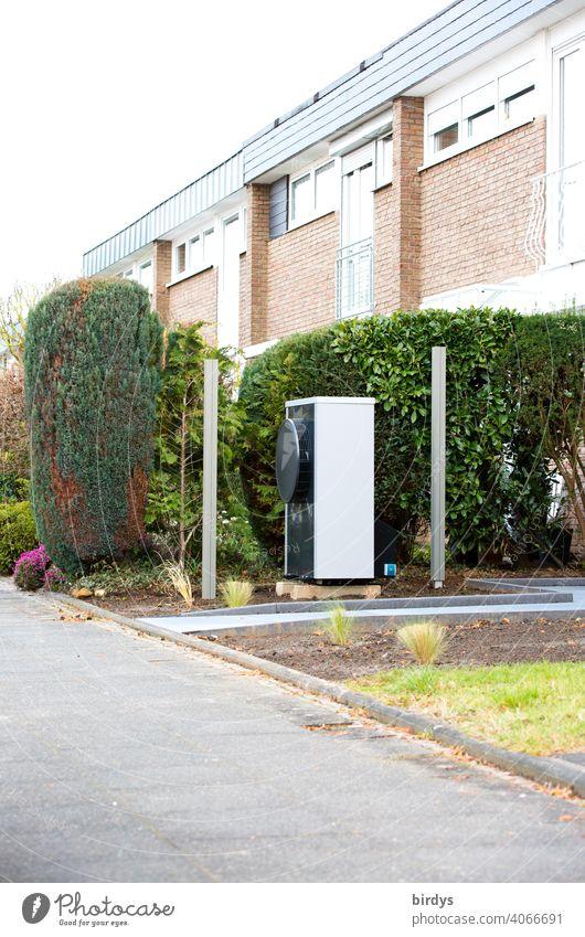 Luftwärmepumpe im Vorgarten eines Reihenhauses. Moderne, umweltfreundliche Heiztechnik Heizung heizen Luftwasserwärmepumpe Nachhaltigkeit Wohnhaus nachhaltig