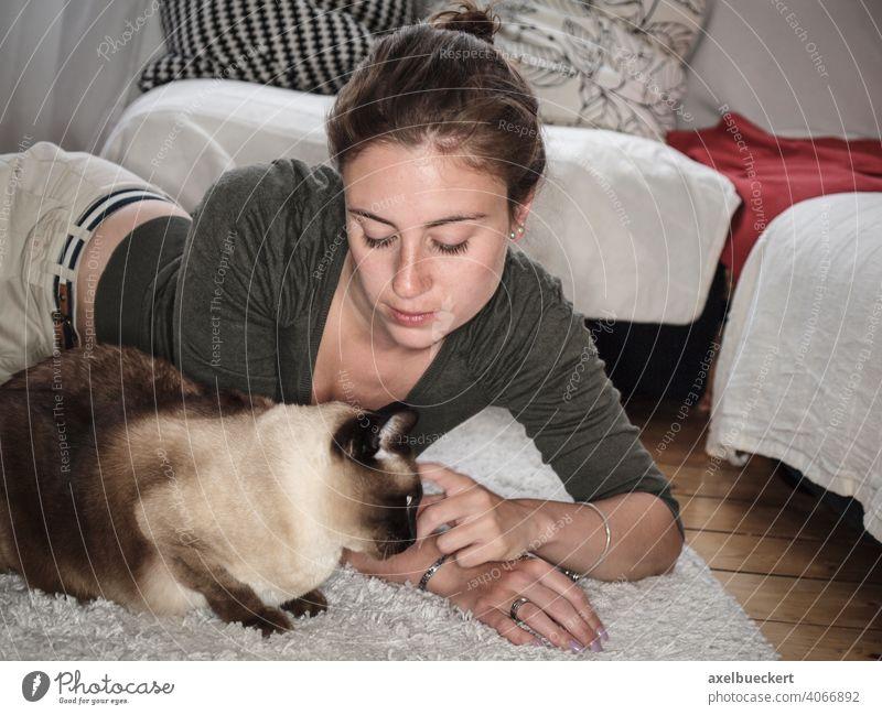 Junge Frau krault ihre Siamkatze auf dem Boden liegend Katze Haustier gemütlich zu Hause Kraulen Streicheln kuscheln Lifestyle entspannend Erholung