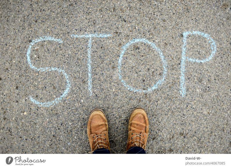 Stop - Hinweis - Kreide auf dem Boden Wort anhalten Achtung Mensch Stillstand stopp Einschnitt verbot
