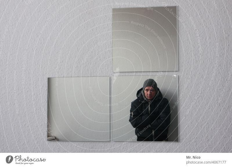 Spiegelbild Mann Reflexion & Spiegelung Selbstportrait Oberkörper Porträt Blick Wand grau kalt Jacke Mütze Innenaufnahme verschränkte Arme außergewöhnlich