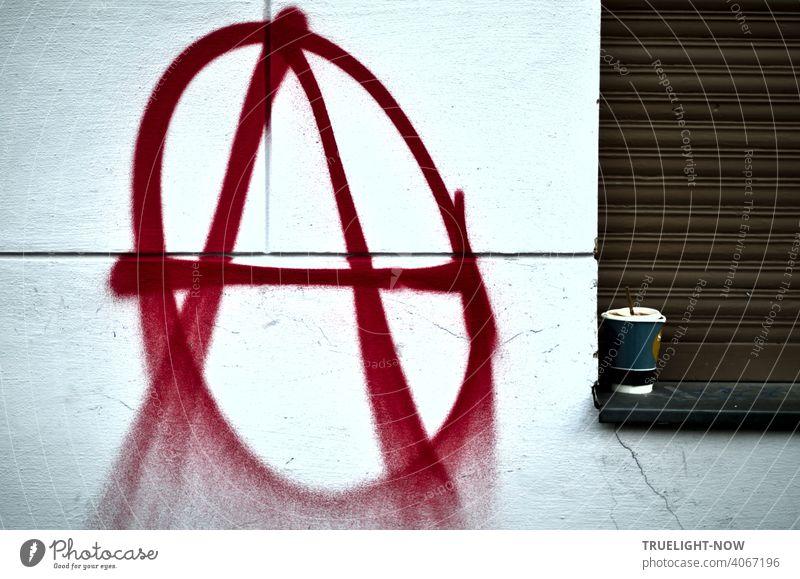 Ein Sprayer hat auf eine weisse Hauswand groß und in roter Farbe das bekannte Signet der Anarchisten oder Anarchos gesprüht: großes A im Kreis. Der  Kaffeebecher auf der Fensterbank daneben vor geschlossenem braunem Rolladen wirkt passend