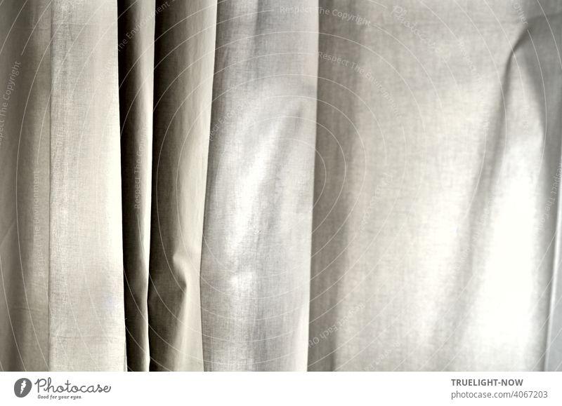 Ein Vorhang aus einfacher weisser Baumwolle hängt in senkrechten Falten und zeigt so eine Vielfalt an fein abgestuften Grautönen Stoff schwarz grau Abstufung