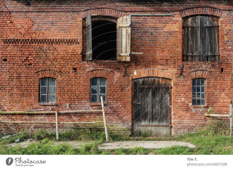 die Fassade eines Stallgebäudes stallung Bauernhof Landwirtschaft Farbfoto Menschenleer Außenaufnahme Tag Hof agriculture Scheune Gebäude Dorf Tür ländlich Wand