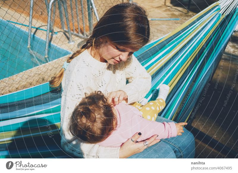 Junge Frau, die ihr Baby auf einer Hängematte sitzend pflegt Mama Familie Feiertage Pflege Liebe heimwärts im Freien Tagespflege Pool Umarmung tagsüber Routine