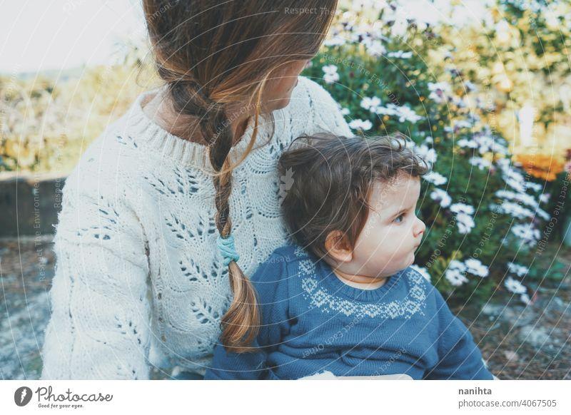 Junge Mutter umarmt ihr Baby und genießt einen Frühlingstag im Garten Familie Mama Lifestyle Liebe Pflege Kind Kindheit Blumen Natur natürlich Hippie im Freien