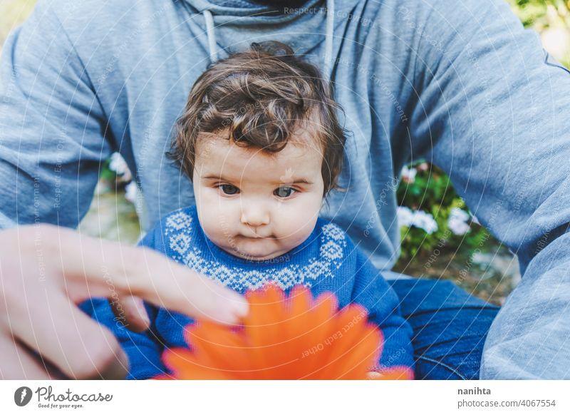 Kleines Baby, das zum ersten Mal eine riesige Blume entdeckt entdecken Frühling Fröhlichkeit Familie Familienzeit Papa Vater Mädchen Kind Kleinkind 9 Monat