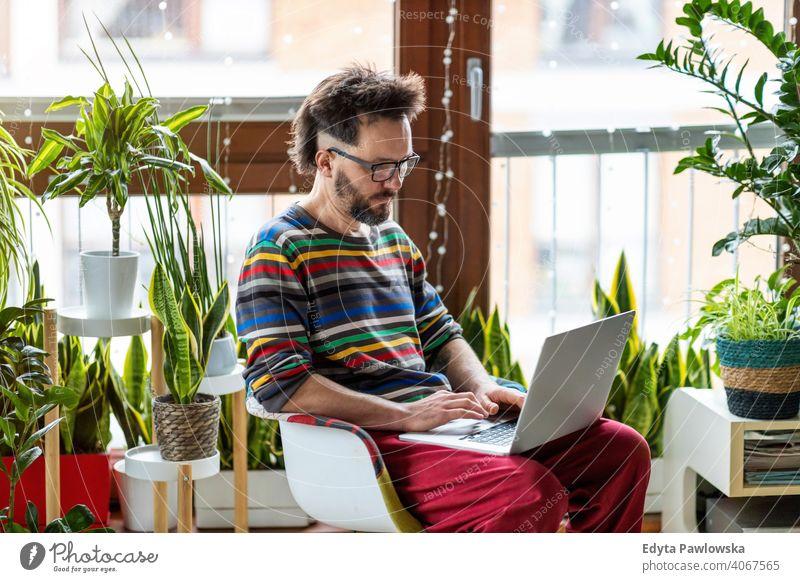 Junger Mann arbeitet zu Hause mit Laptop umgeben von Zimmerpflanzen online Onlinebanking Online-Lernen Online-Shopping Büro heimwärts Hand freiberuflich Mobile