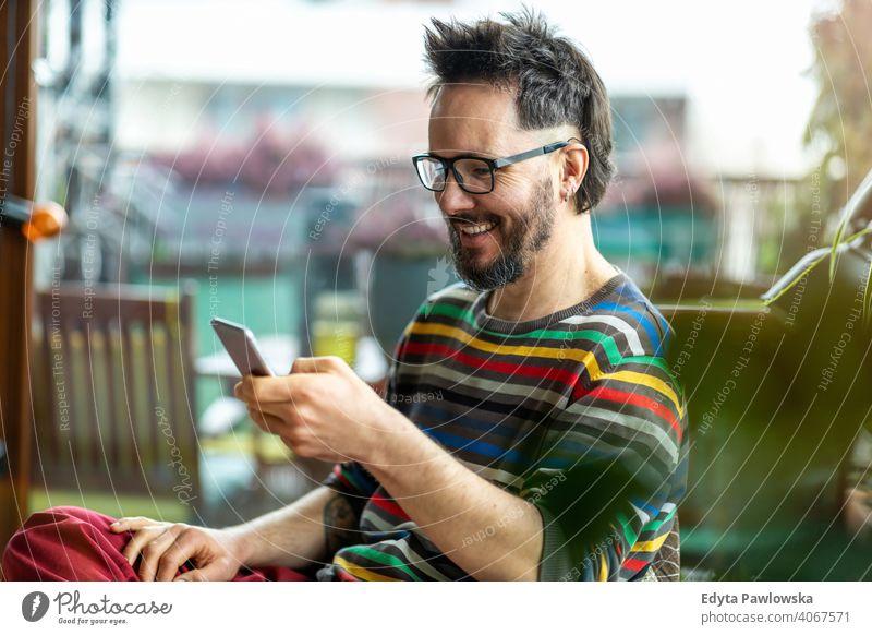 Glücklicher Mann, der ein Mobiltelefon zu Hause benutzt Arbeit Freiberufler Blogger Typ Anruf Texten online Kaukasier elektronisch Netzwerk digital Kunde