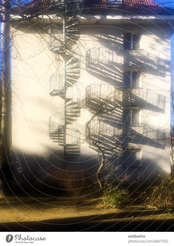 Eine Wendeltreppe und ihr Schatten außen brandmauer fassade fenster haus himmel himmelblau hof innenhof innenstadt mehrfamilienhaus menschenleer mietshaus