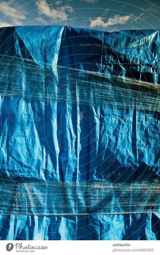 Blaue Plane plane folie verpackung eingewickelt paket versand schutz regenschutz wetterschutz eingeschnürt material kunststoff gewebe blau