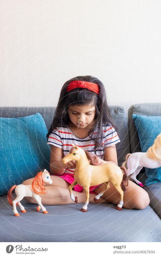 Kleines Mädchen spielt mit ihren Spielzeugpferden auf dem Sofa allein Appartement Schwarzes Haar sorgenfrei Freizeitkleidung Kind Kindheit Farbbild bequem