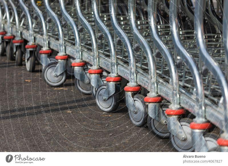 Einkaufswagen, die auf dem Parkplatz und im Eingangsbereich eines riesigen Lagerhaus-Supermarktes am Rande der Stadt Zaragoza, Spanien, angeordnet sind.