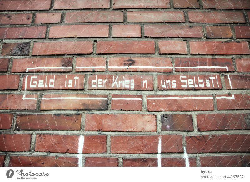 Kapitalismus-Kritik auf Backstein: Geld ist der Krieg in uns selbst Egoismus Sozialismus sozial unsozial Philosophie Ethik Haltung Einstellung selbstreflektion