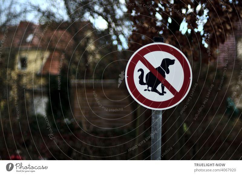 Ein auffälliges Verbotsschild für Menschen mit kackendem Hund vor der Gartenanlage. Im unscharfen Hintergrund Bäume, Sträucher, ein Gartenhaus und ein gelb leuchtendes Wohnhaus