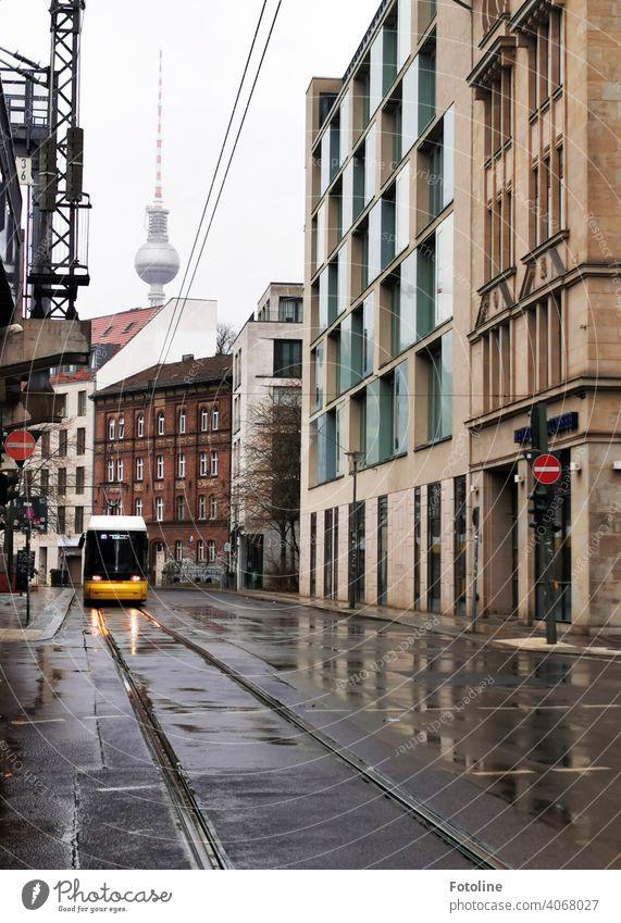 Berlin von seiner grauen Seite. Auch der Fernsehturm versteckt sich im Grau in Grau. Nur die Straßenbahn leuchtet knall gelb. Außenaufnahme Farbfoto Hauptstadt