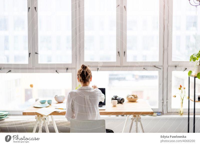 Rückansicht einer jungen Frau, die in einem Loft-Büro an einem Laptop arbeitet Jahrtausende Schüler Hipster im Innenbereich Fenster natürlich Mädchen