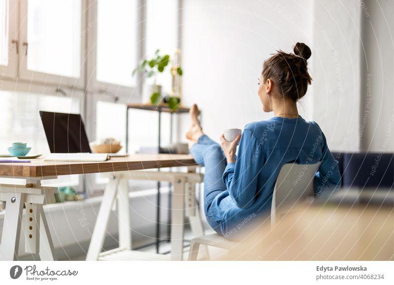 Junge Frau entspannt im Büro mit ihren nackten Füßen auf dem Schreibtisch Jahrtausende Schüler Hipster im Innenbereich Loft Fenster natürlich Mädchen