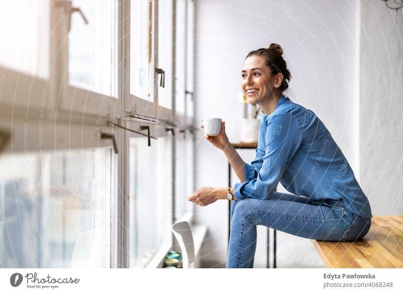 Junge Frau trinkt Kaffee und schaut aus dem Fenster Jahrtausende Schüler Hipster im Innenbereich Loft natürlich Mädchen Erwachsener eine attraktiv gelungen