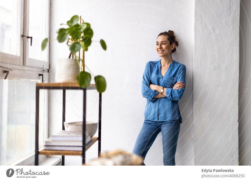 Porträt einer lächelnden kreativen Frau in einem modernen Loft-Raum Jahrtausende Schüler Hipster im Innenbereich Fenster natürlich Mädchen Erwachsener attraktiv