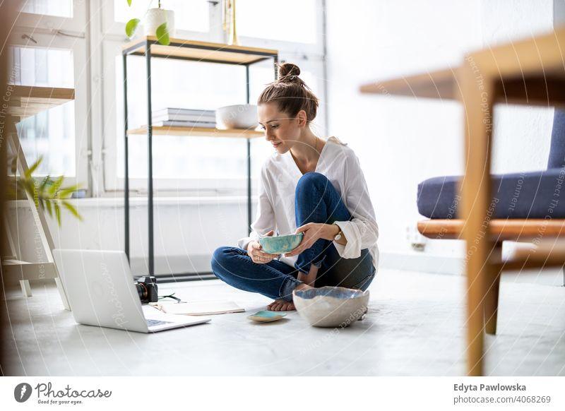 Junge Töpferin mit Laptop in ihrer Werkstatt Internet online Computer Technik & Technologie Einzelhändlerin Einzelhandel Töpferwaren Artikel Verkauf Sitzen