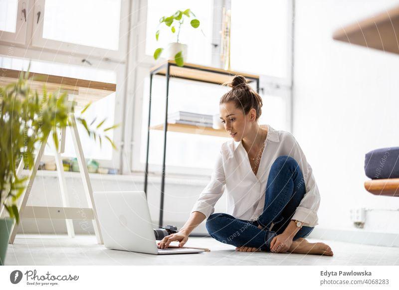 Kreative junge Frau arbeitet am Laptop in ihrem Studio Jahrtausende Schüler Hipster im Innenbereich Loft Fenster natürlich Mädchen Erwachsener eine attraktiv