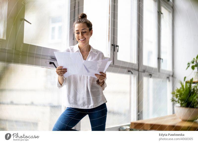 Junge Geschäftsfrau schaut auf Papierkram in einem Büro Jahrtausende Schüler Hipster im Innenbereich Loft Fenster natürlich Mädchen Erwachsener attraktiv