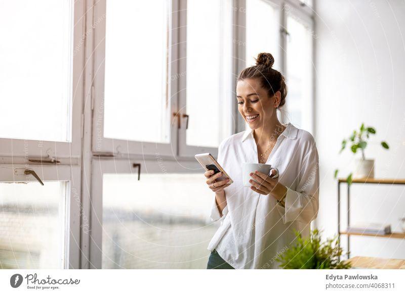 Kreative Geschäftsfrau mit Smartphone im Loft-Büro Jahrtausende Schüler Hipster im Innenbereich Fenster natürlich Mädchen Erwachsener eine attraktiv gelungen