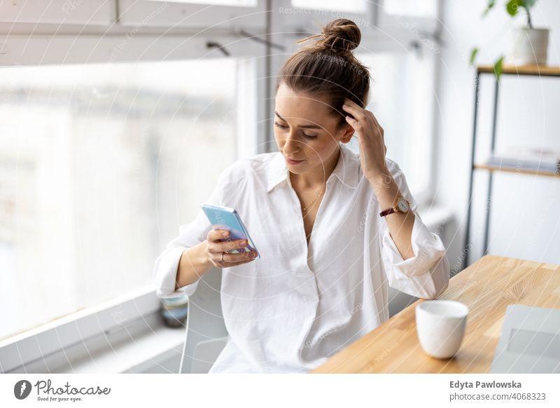 Aufnahme einer jungen Geschäftsfrau mit Smartphone in einem Büro Jahrtausende Schüler Hipster im Innenbereich Loft Fenster natürlich Mädchen Erwachsener