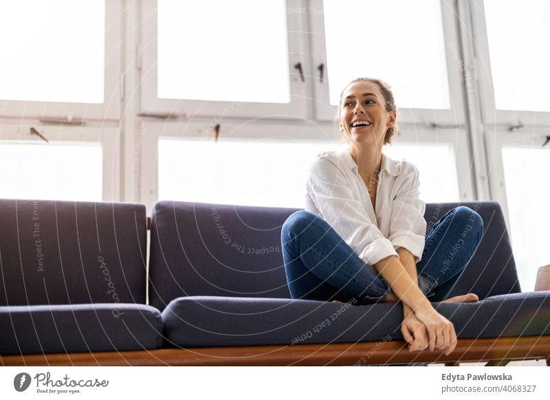 Junge Frau entspannt auf Sofa Sitzen Liege aussruhen entspannend bequem Pause Barfuß Lotos Yoga Meditation Jahrtausende Schüler Hipster im Innenbereich Loft