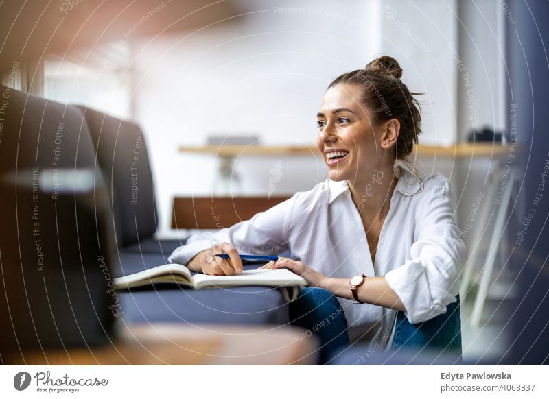 Junge Frau macht Hausaufgaben auf dem Sofa Sitzen Liege aussruhen entspannend bequem Jahrtausende Schüler Hipster im Innenbereich Loft Fenster natürlich Mädchen