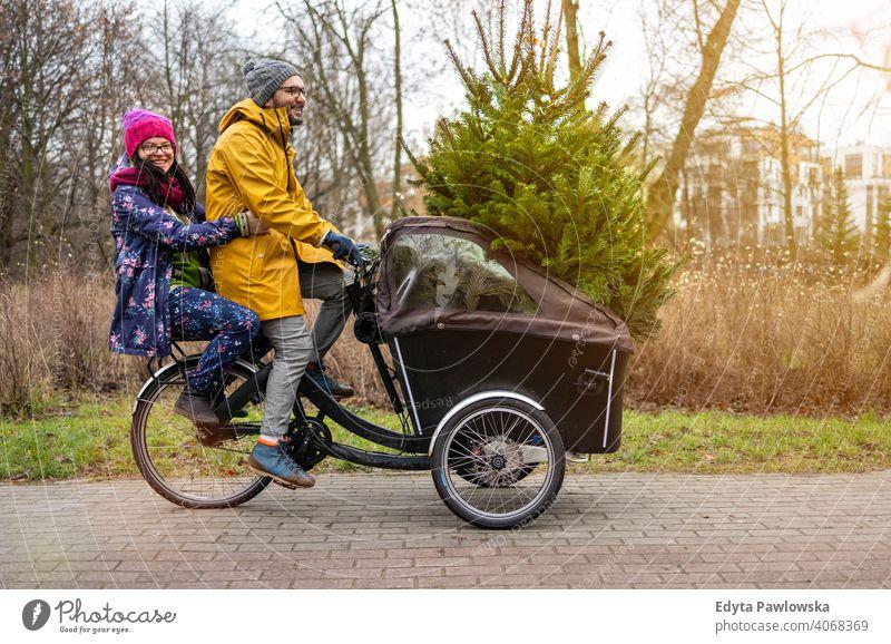 Paar hat eine Fahrt mit Fracht Fahrrad transportieren Weihnachtsbaum nachhaltiger Transport Baum Spaß Freude genießend Hipster modern transportierend tragen