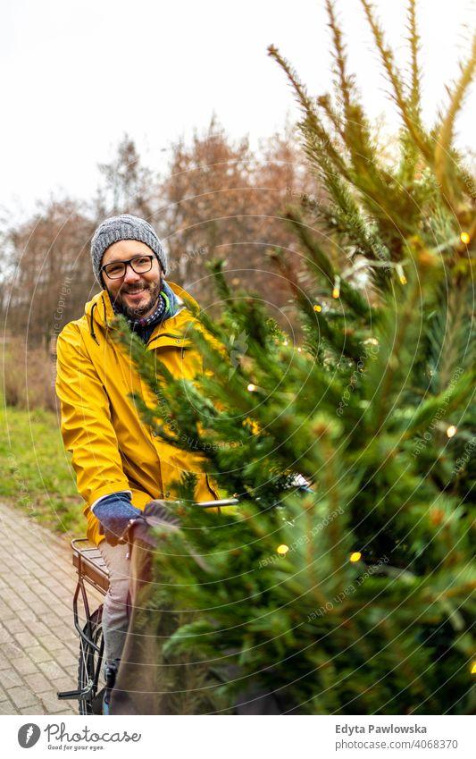 Mann transportiert Weihnachtsbaum auf Fahrrad nachhaltiger Transport Baum Spaß Freude genießend Hipster modern transportierend tragen tausendjährig Winter