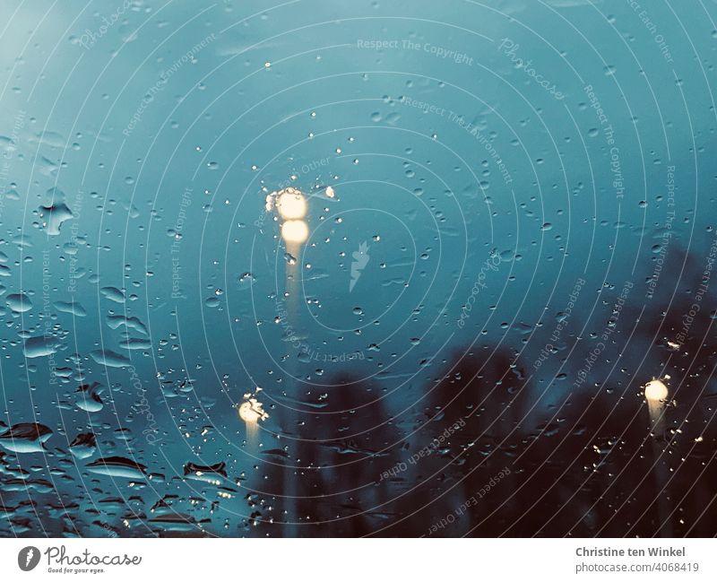 Blick durch ein nasses Fenster auf die Abenddämmerung zur blauen Stunde. Regenwetter mit verschwommenen Bäumen und Straßenlaternen verregnet Dämmerung