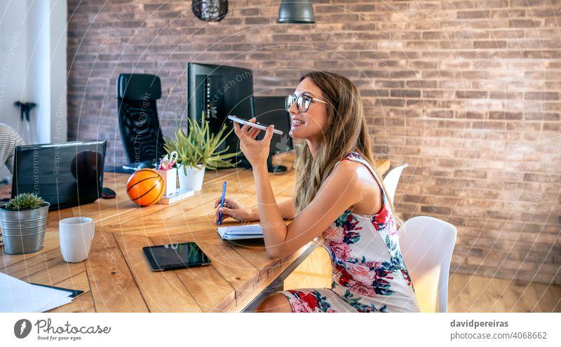Büroangestellter, der mit einem Mobiltelefon mit Lautsprecher spricht Geschäftsfrau sprechender Lautsprecher Handy Mobile Mitteilung Business Gespräch Menschen