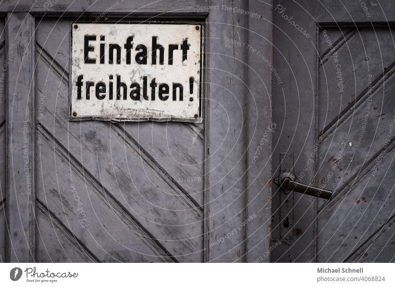 Einfahrt freihalten! einfahrt freihalten Einfahrtstor auffordern Aufforderung Tür grau Schwarzweißfoto schwarzweiß Schilder & Markierungen