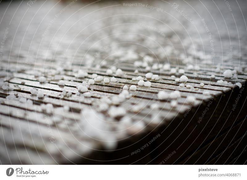 Hagelkörner auf einer Holzterrasse hagel eis Hagelkorn schnee Klimawandel hagelkörner Hagelsturm wetter kalt Hagelschlag kälte frost Hagelschaden Hagelschauer