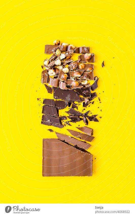 Variation von Schokolade Stücken auf einem gelben Hintergrund variation Nuss Süßwaren Studioaufnahme Stil Ernährung Farbfoto Zucker braun Foodfotografie