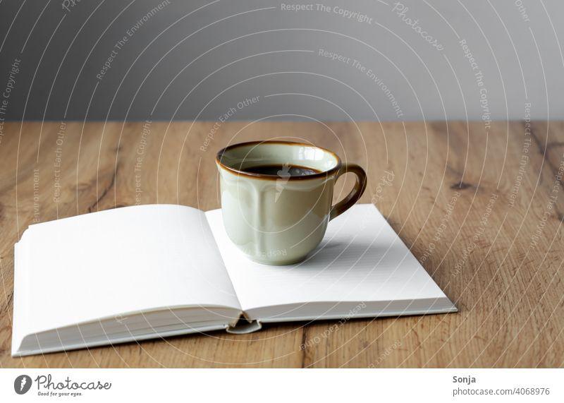 Eine rustikale Kaffeetasse auf einem offenen Buch Tasse Getränk Kaffeepause Frühstück aromatisch Morgen heiß braun alt Koffein Espresso Tisch Emaille schwarz