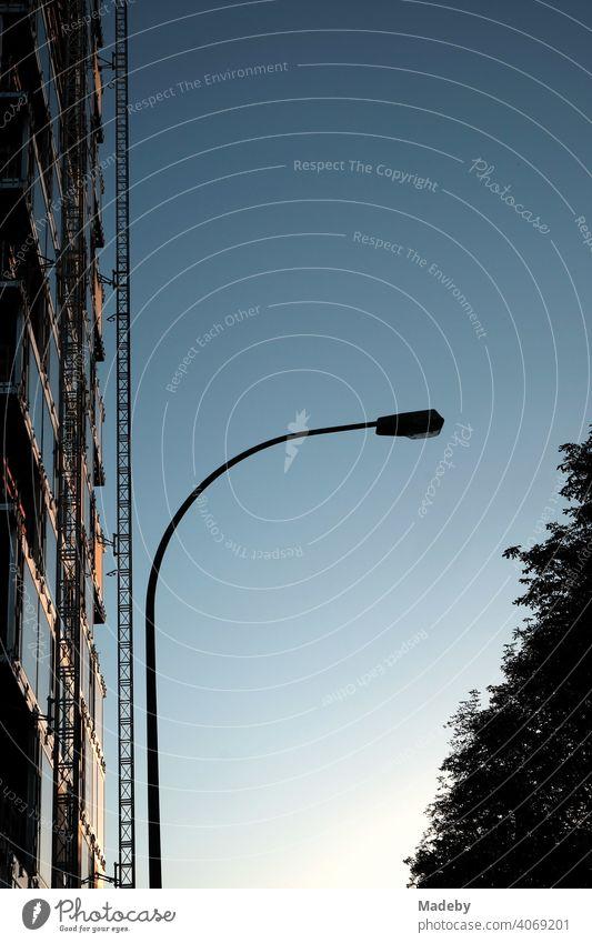 Geschwungene Straßenlaterne vor blauem Himmel mit der Fassade eines Hochhaus mit Gerüst im Rohbau im Licht der Abendsonne am Grüneburgpark im Westend von Frankfurt am Main in Hessen