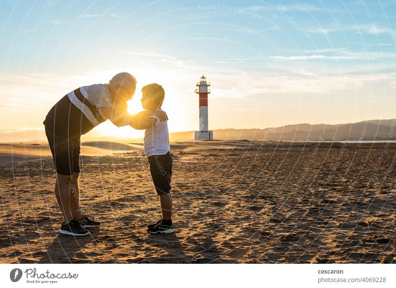 Großvater und Enkel umarmen sich an einem Strand mit einem Leuchtturm im Hintergrund Rücken Junge Kind Kindheit Kinder Küste Papa Tag älter Familie Fangar