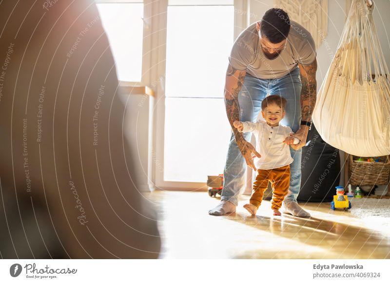 Kleiner Junge lernt laufen mit seinem Vater neben ihm zu Hause alleinerziehend alleinerziehender Vater Vatertag Vaterschaft zu Hause bleiben Dad