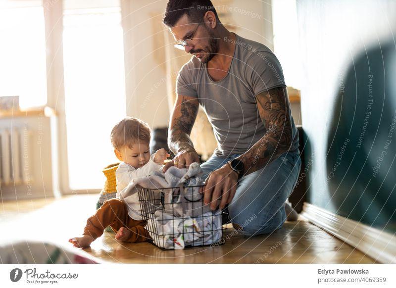Vater und Sohn machen Wäsche zusammen alleinerziehend alleinerziehender Vater Vatertag Vaterschaft zu Hause bleiben Dad Vaterschaftsurlaub moderne Männlichkeit