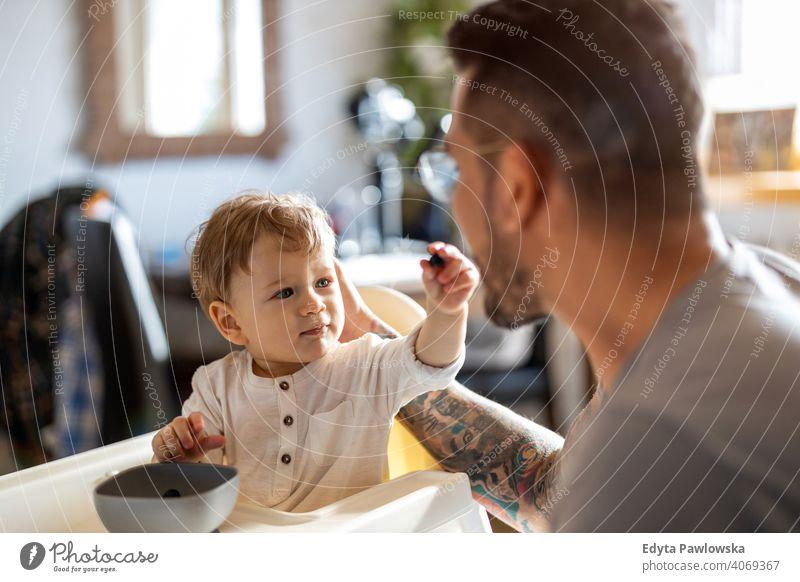 Alleinerziehender Vater füttert sein Baby, das in einem Hochstuhl sitzt alleinerziehend alleinerziehender Vater Vatertag Vaterschaft zu Hause bleiben Dad